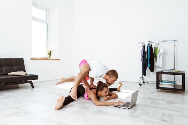 Jovem casal esportivo bonito treinamento yoga asanas em casa.