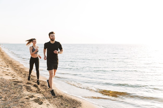 Jovem casal esportivo correndo juntos na praia