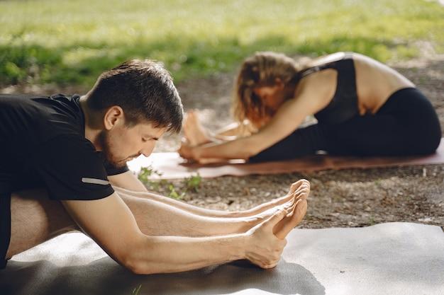 Jovem casal esportivo fazendo ioga fitness. pessoas em um parque de verão.