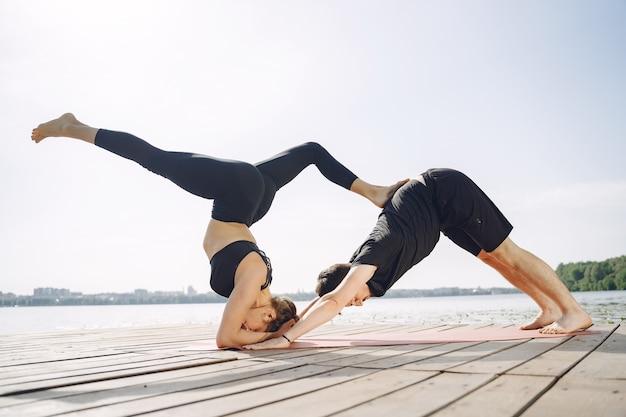 Jovem casal esportivo fazendo ioga fitness. pessoas perto da água.