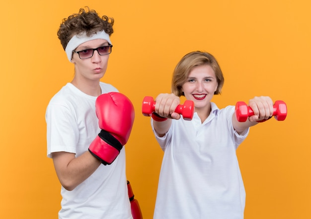 Jovem casal esportivo mulher com halteres ao lado do namorado e luvas de boxe posando sobre laranja