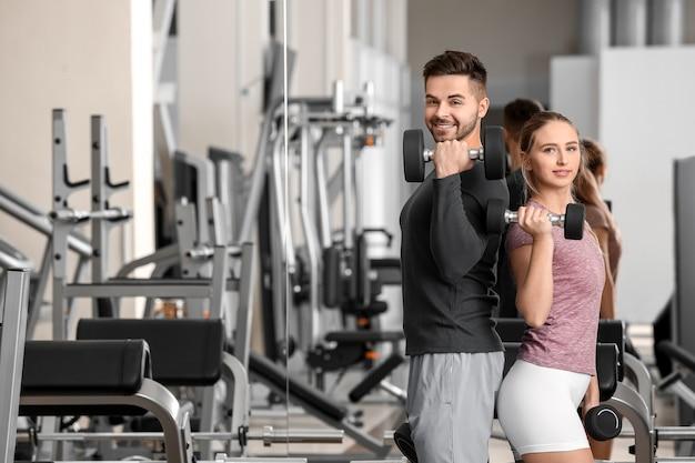 Jovem casal esportivo treinando com halteres na academia