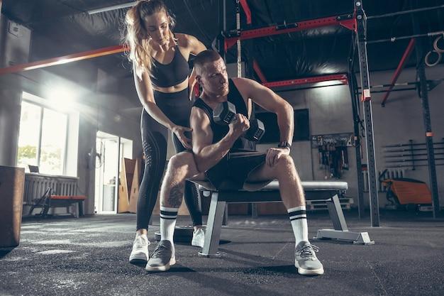 Jovem casal esportivo treinando na academia juntos
