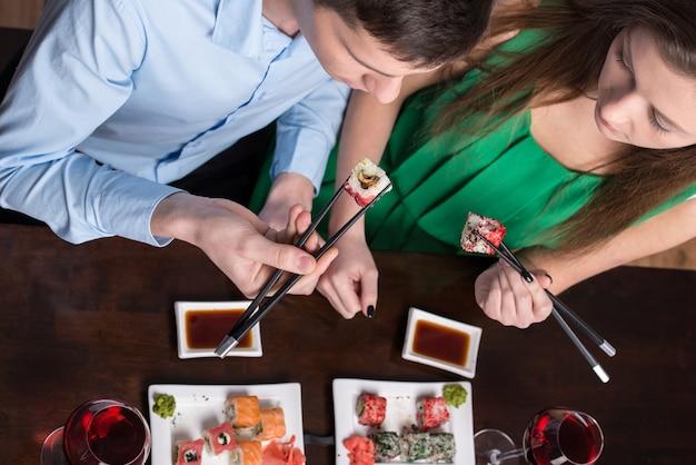 Jovem casal está comendo sushi no restaurante.