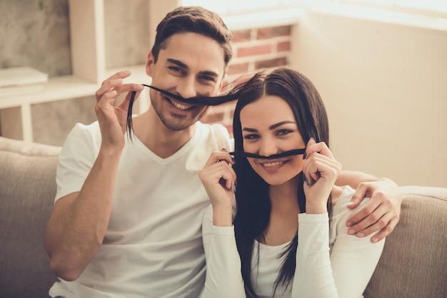 Jovem casal está fazendo bigode de cabelo