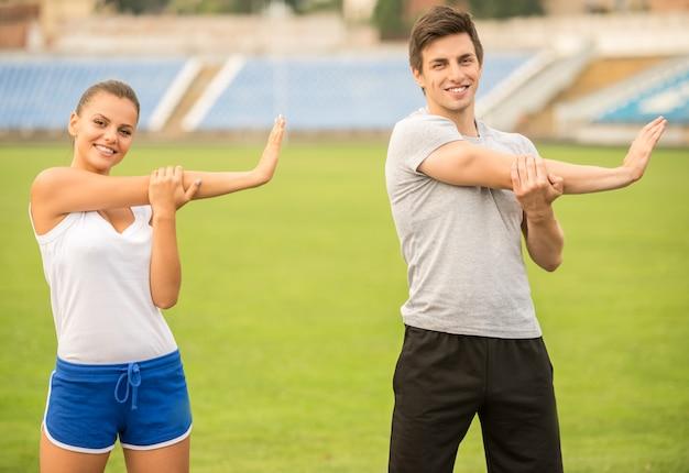 Jovem casal está fazendo exercícios, estendendo-se no estádio.