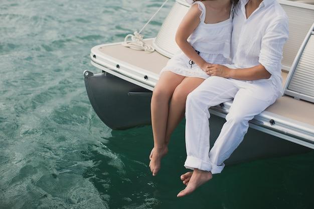 Jovem casal está navegando em um iate no oceano índico. homem e mulher sentados na borda do iate