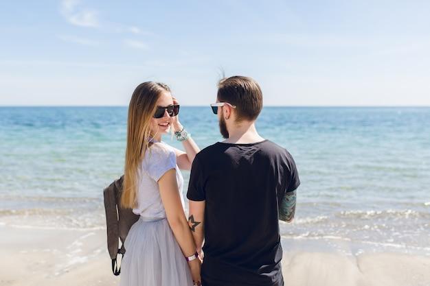 Jovem casal está parado perto do mar
