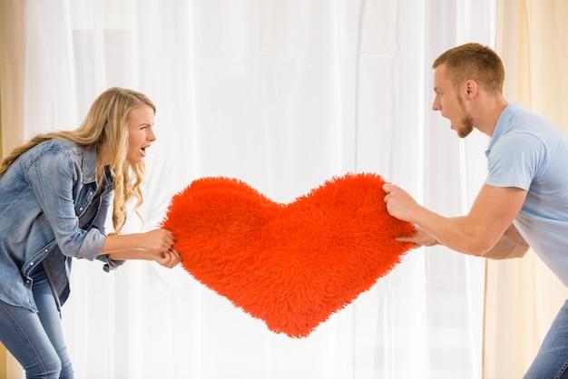 Jovem casal está puxando o coração para o outro.