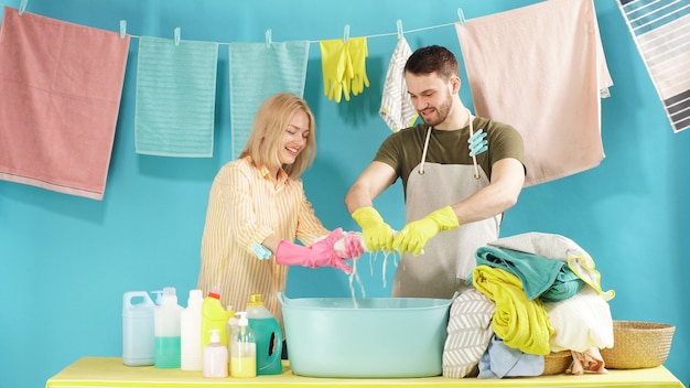 Jovem casal está se divertindo na lavanderia. tarefas domésticas