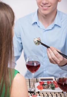 Jovem casal está sentados juntos e comendo sushi.