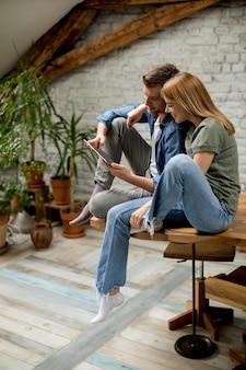 Jovem casal está usando um tablet digital e sorrindo na cozinha em casa