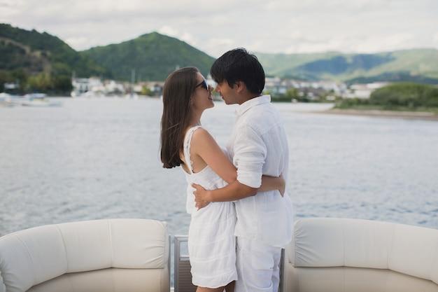 Jovem casal está viajando em um iate no oceano índico. homem e mulher ficam na beira do barco e se beijam