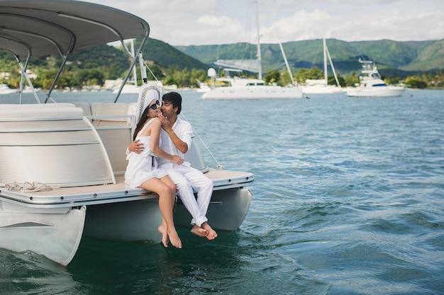Jovem casal está viajando em um iate no oceano índico. homem e mulher sentam-se na beira do barco e se beijam