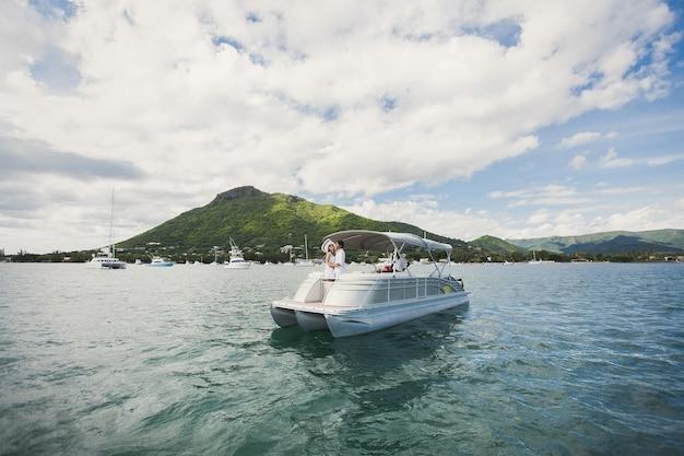 Jovem casal está viajando em um iate no oceano índico. na proa do barco, uma família amorosa se abraça
