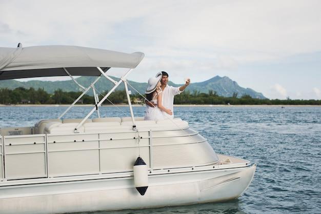 Jovem casal está viajando em um iate no oceano índico. na proa do barco, uma família amorosa tira uma selfie.