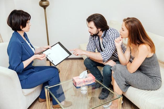 Jovem casal está visitando psicólogo. eles estão sentados e olhando à mão desenhando com muito cuidado. médico está explicando o significado desta imagem.