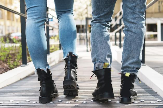 Jovem casal estiloso com botas de couro caminhando pela estrada