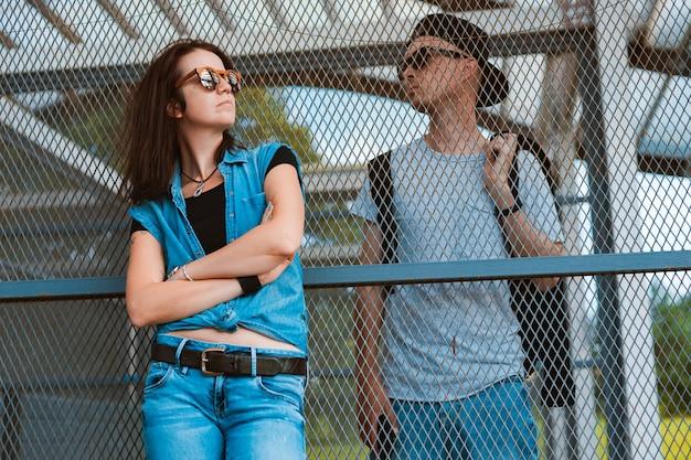 Jovem casal estiloso com óculos de sol em uma cerca separada