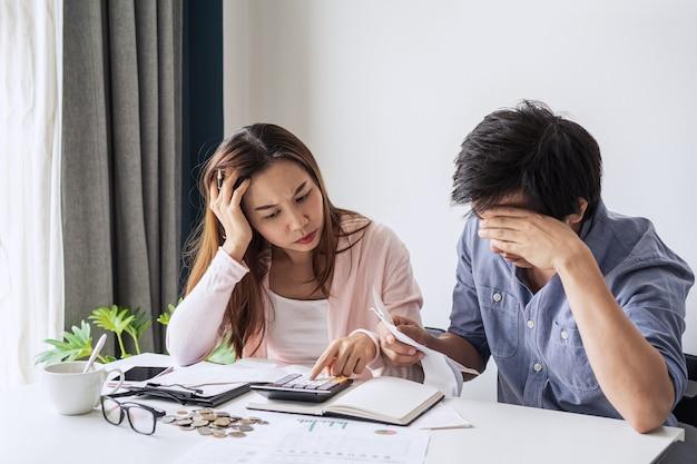 Jovem casal estressado calculando as despesas mensais da casa