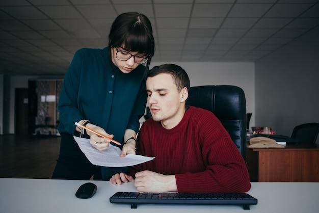 Jovem casal estudantes cara e menina olhando cuidadosamente os papéis. garota de óculos, explicando algo cara.