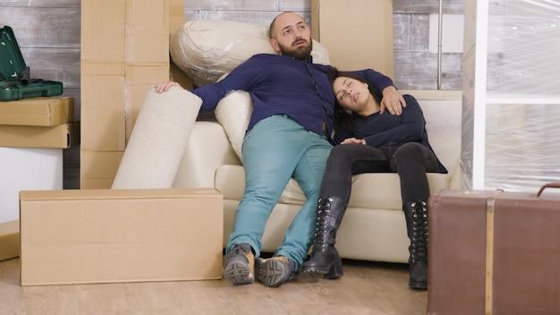 Jovem casal exausto depois de carregar um monte de caixas em seu novo apartamento. casal se espatifando no sofá.
