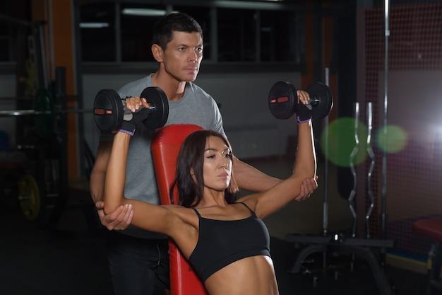 Jovem casal exercícios com halteres juntos no ginásio. estilo de vida ativo, homem e mulher no clube de fitness