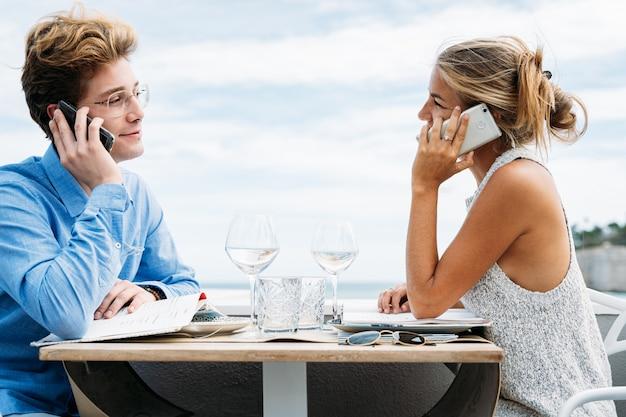 Jovem casal falando ao telefone, sentado em uma mesa de restaurante