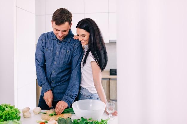 Jovem casal familiar alegre cozinhando o jantar, cortando a salada de legumes fresca, se divertindo juntos no interior da cozinha moderna, casal romântico e feliz se unindo rindo, ajudando a preparar uma refeição saudável