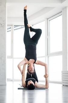 Jovem casal fazendo acro yoga em par