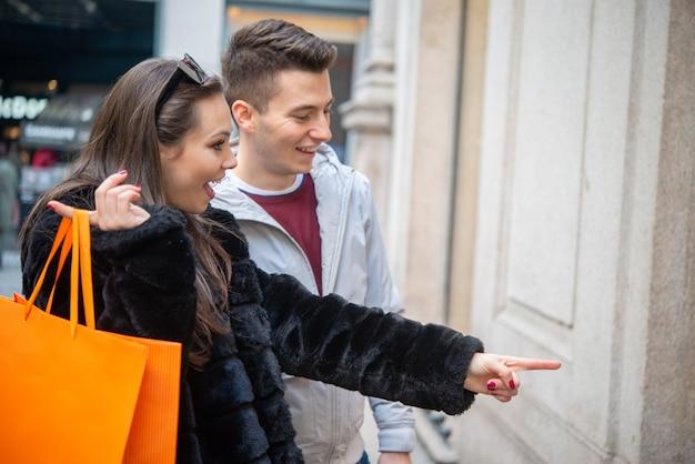 Jovem casal fazendo compras juntos em uma rua urbana