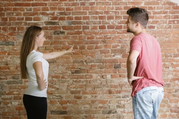 Jovem casal fazendo conserto de apartamento juntos. homem casado e mulher fazendo reforma ou reforma em casa. conceito de relações, família, amor. discuta pintar a parede ou prepará-la para isso.
