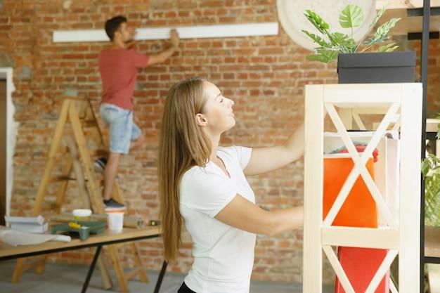 Jovem casal fazendo conserto de apartamento juntos.