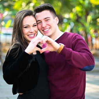 Jovem casal fazendo formato de coração com as mãos