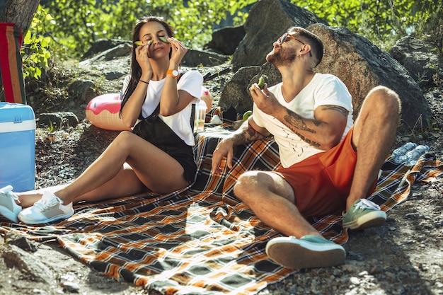 Jovem casal fazendo piquenique à beira do rio em dia ensolarado.