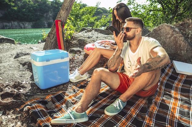 Jovem casal fazendo piquenique à beira do rio em um dia ensolarado