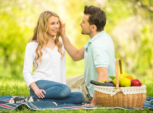 Jovem casal fazendo piquenique no gramado no parque de verão.