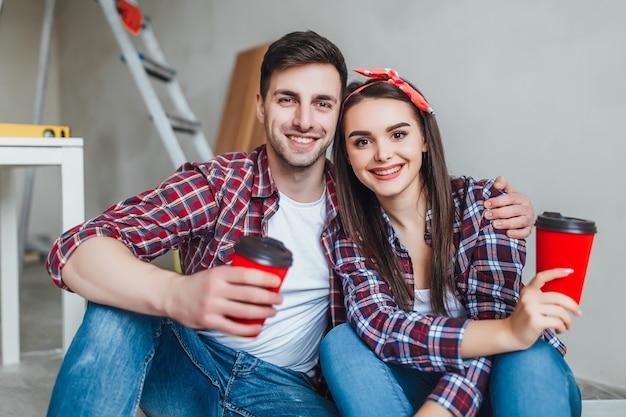 Jovem casal fazendo reparos, tem um tempo de pausa com uma xícara de café saboroso. eles estão se abraçando em uma nova casa