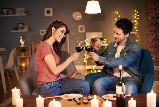 Jovem casal fazendo um brinde para uma noite adorável