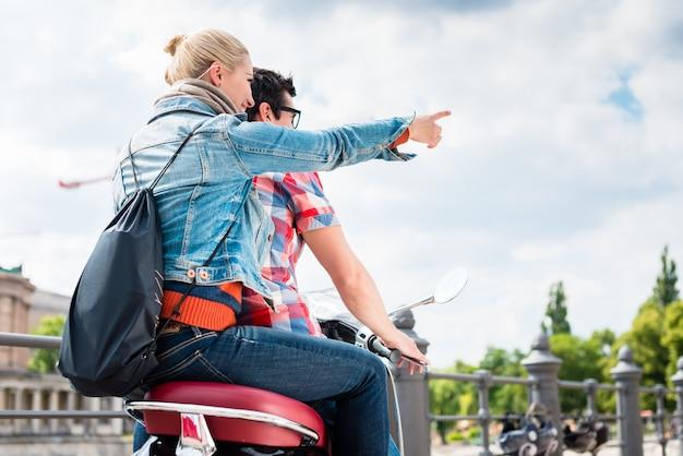 Jovem casal fazendo uma viagem de scooter para a ilha dos museus de berlim