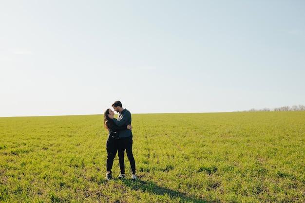 Jovem casal feliz abraçando em um prado verde com céu azul ao fundo.
