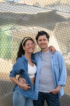 Jovem casal feliz abraçando o retrato de um homem elegante e uma mulher com roupas da moda de rua