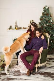 Jovem casal feliz abraços adorável cão akita inu enquanto sente-se na poltrona retrô elegante para férias de natal em casa, árvore de natal e lareira, aconchegante decoração de casa
