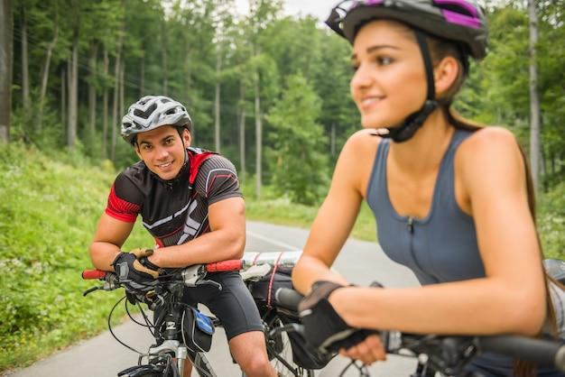 Jovem casal feliz andando de bicicleta na estrada da floresta.