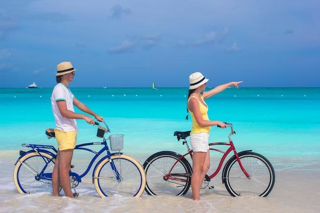 Jovem casal feliz andando de bicicleta na praia tropical branca