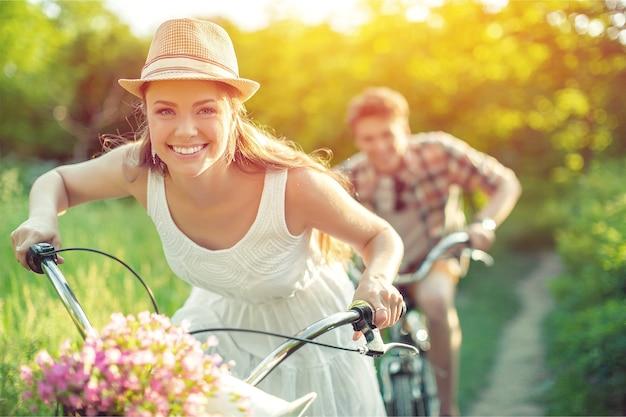 Jovem casal feliz andando de bicicleta pelo parque