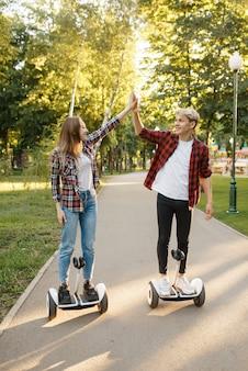 Jovem casal feliz andando na placa do giroscópio no parque de verão.