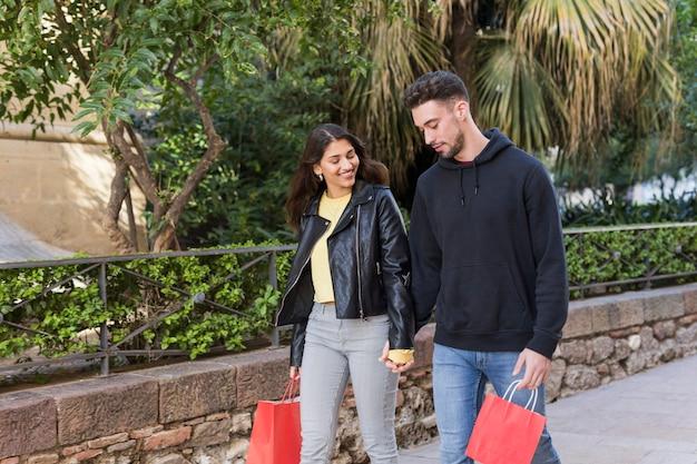 Jovem casal feliz andando na rua perto de árvores