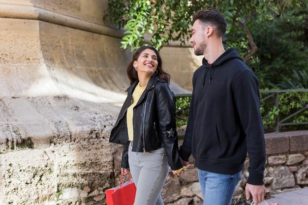 Jovem casal feliz andando na rua perto de plantas