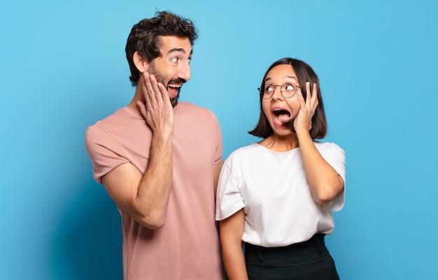 Jovem casal feliz, animado e surpreso, olhando para o lado com as duas mãos no rosto